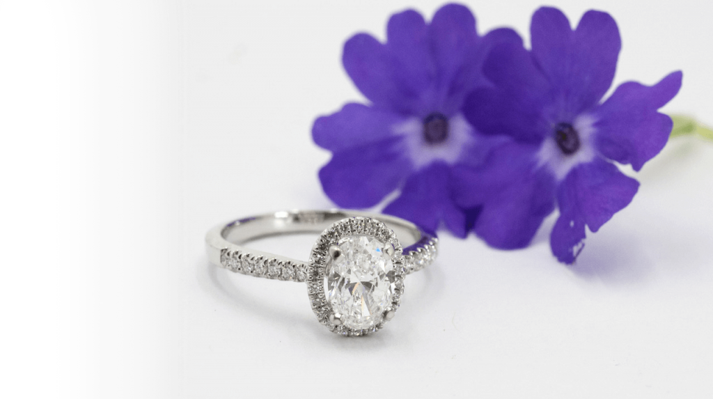 Diamond engagement ring sitting next to some blooming flowers